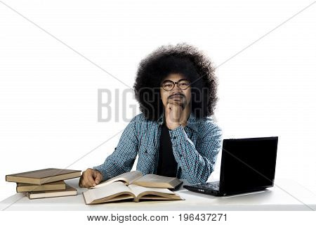 Afro male college student thinking an idea while studying with a laptop and textbooks on the desk