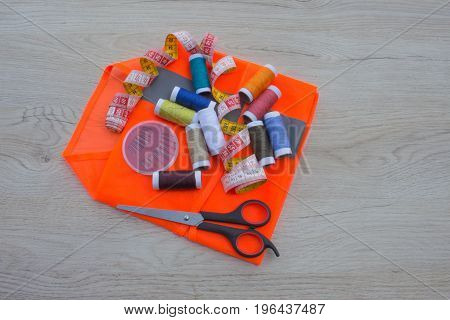 Sewing still life: colorful cloth. Sewing kit includes threads of different colors thimble and other sewing accessories on wooden table. tools for sewing for hobby