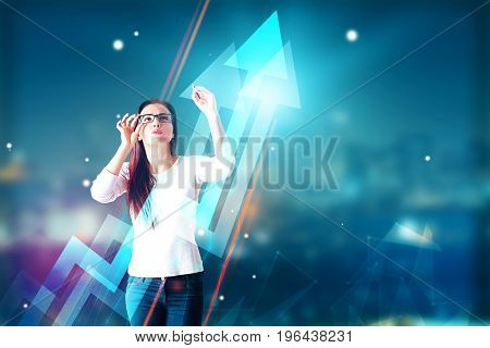 Thoughtful young woman with glasses drawing abstract upward chart arrows on blurry night city background with copy space. Profit concept. Double exposure