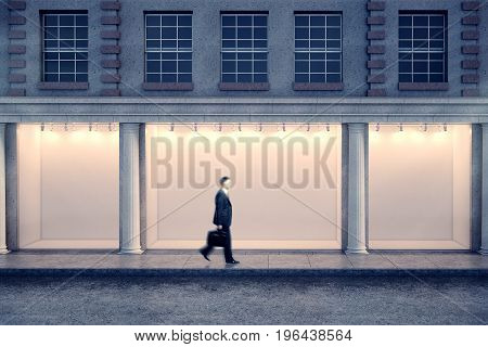 Side view of blurry businessman passing building with illuminated clear storefront and columns in night city. Advertisement and commerce concept. Mock up 3D Rendering