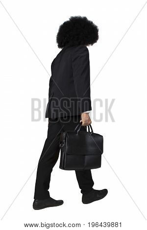 Portrait of businessman with frizzy hair walking in the studio while carrying briefcase