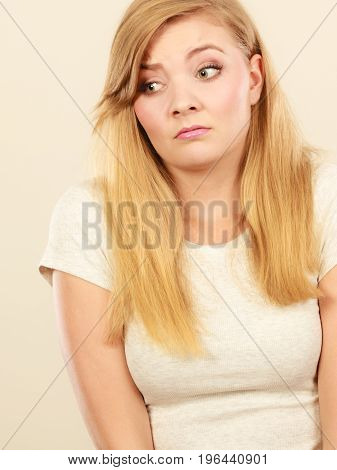 Face expression emotions concept. Sad cute young blonde attractive woman in white t shirt.