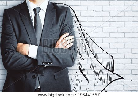Businessman with drawn cape on brick wall background. Leadership concept