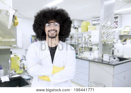 Confident male scientist in protective glasses and lab coat standing with crossed arms and looking at camera in the lab
