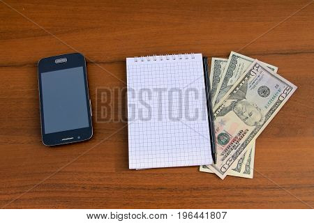 Notepad With Pen, Smartphone And Dollar Cash On Wooden Desk