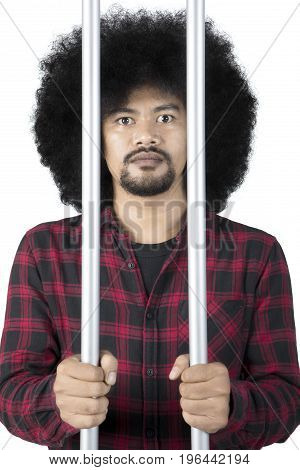 Portrait of african criminal looking at camera from behind the bars in prison