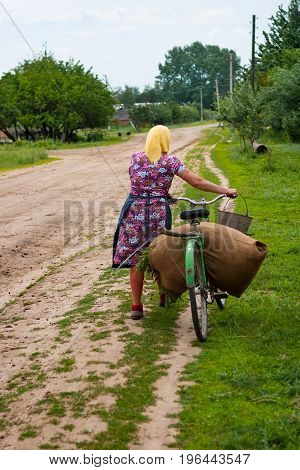 Summer day. In the frame a grandmother a villager pushes a bicycle. On the bike is an old huge bag of grass for livestock. Black and white image