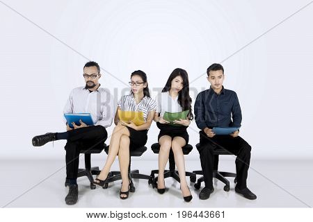 Group of multiracial employees sitting on the chair while holding their documents and waiting for job interview