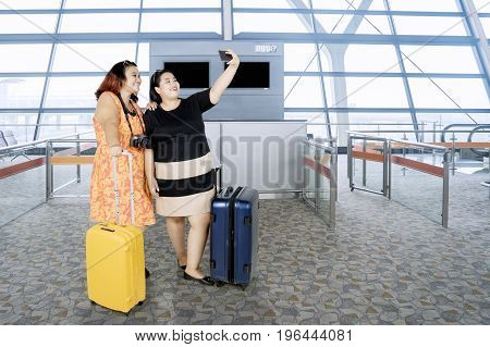 Two fat women taking a selfie photo by using smartphone while standing with a suitcase in the airport terminal