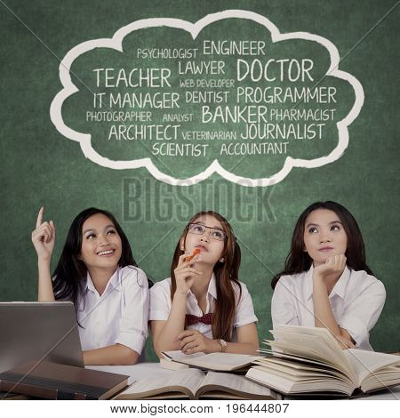 Three female high school students sitting in the class while thinking their dreams job on speech bubble