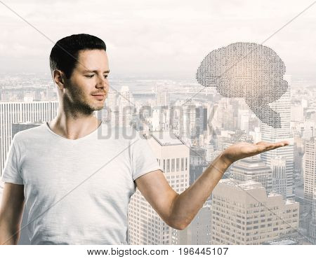 Handsome young guy holding abstract digital human brain on city background. Artificial intellect concept