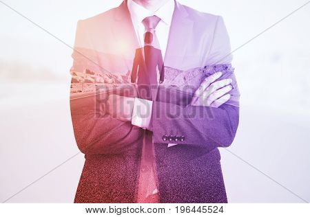 Young businessman with folded arms thinking about way to success. Future concept. Toned image. Double exposure
