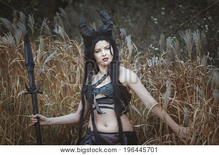 Beautiful wild girl with horns stands in the thickets