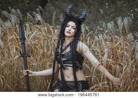 Portrait of a savage girl with horns in the thickets