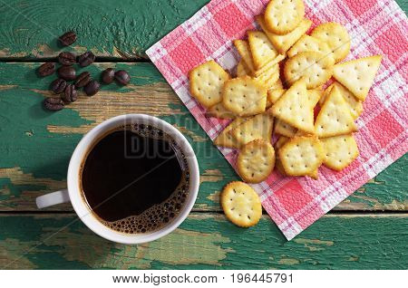Cup of hot coffee and crackers with cheese flavor on green old wooden table top view