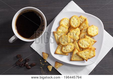 Crackers with cheese flavor and cup of hot coffee on dark wooden table top view