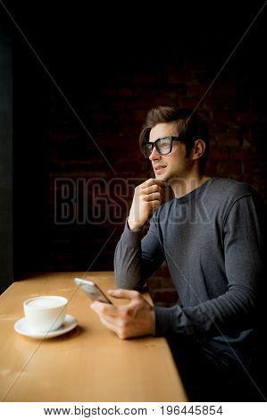Thinking Man Looking In The Window While Drinking Coffee In Morning In Coffee While Using Phone