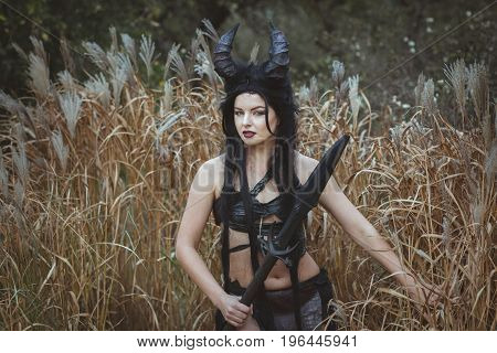 Girl shaman with horns stands in the thickets