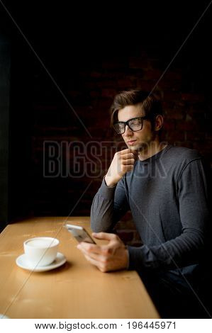 Thinking Man Using His Phone While Drink Coffee