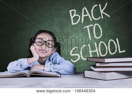 Cute little girl sitting with textbooks on the table and back to school word on the chalkboard