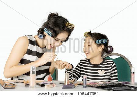 Pretty mother doing makeup while applying nail polish to her daughter isolated on white background