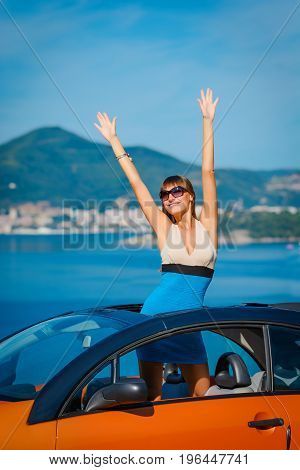 Beautiful Young Woman With Long Hair Standing In Orange Cabriolet At The Mediterranean Sea Coast