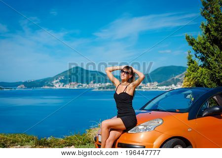 Beautiful Young Woman With Long Hair Sitting On Orange Cabriolet At The Mediterranean Sea Coast