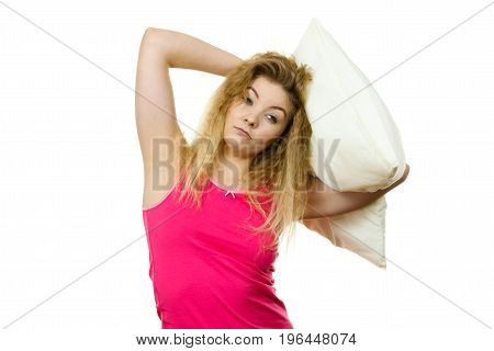 Sleepy woman with blonde tangled hair hugging white pillow feeling tired or hangover. Studio shot isolated