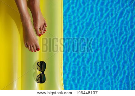 Portrait Of Beautiful Tanned Woman Relaxing In Swimming Pool. Sunglasses And Inflatable Matress. Leg