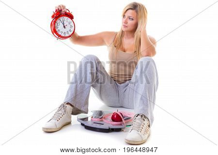 Diet fitness slimming loosing weight concept. Curvy worried woman holding big old fashioned clock sitting on weighing machine