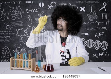 Portrait of researcher examining a microscope slide with chemical fluid on the table. Shot with doodles background on blackboard
