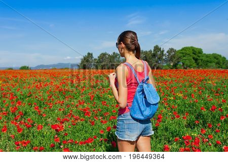 Tourist Woman With Backpack On The Field Of Red Poppies Near Of Girona, Catalonia, Spain Near Of Bar