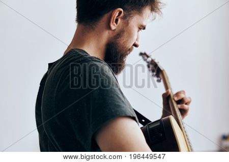 Young guy with a beard on a light background playing the guitar.