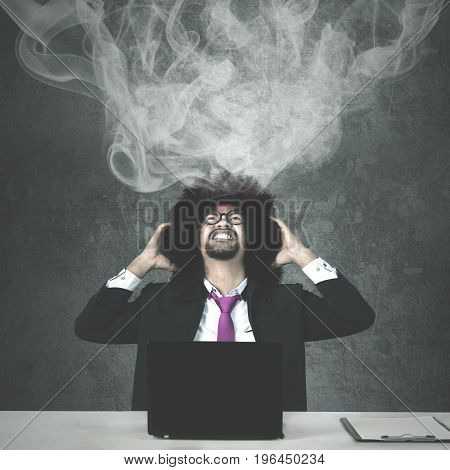 Afro businessman looks stressful with smoke over his head while working with a laptop and clipboard