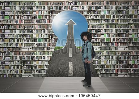 Male Afro student showing thumb up in front of a bookcase with keyhole and upward arrow