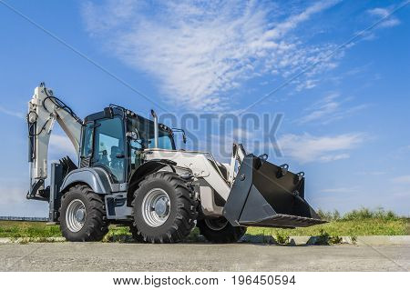 The new tractor is on the road in the city a clear day with blue sky.