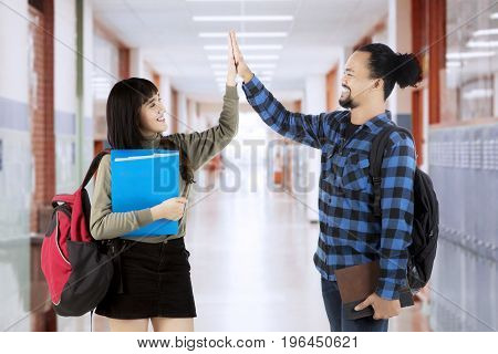 Two high school students giving high five together while standing in the school corridor