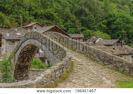a romanesque bridge made of donkey back of of the 17th century at the entrance to the village of Fondo in Piedmont,Italy