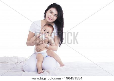 Image of a beautiful mother thinking something while feeding her baby isolated on white background