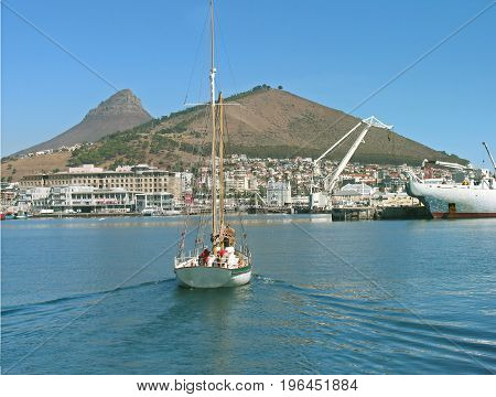 FROM CAPE TOWN, SOUTH AFRICA, A BOAT IN THE FORE GROUND, SAILING TOWARDS LIONS HEAD AND SIGNAL HILL IN THE BACK GROUND