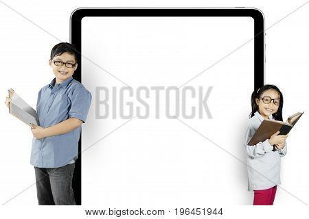 Two elementary students reading a book while standing near a blank billboard isolated on white background