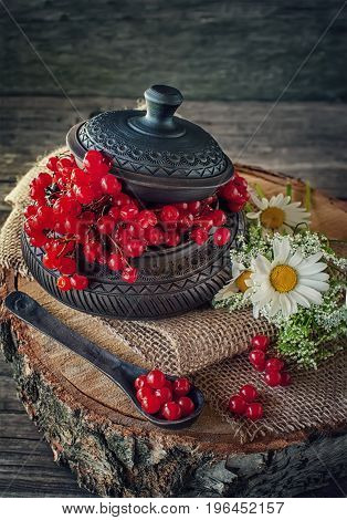 Ripe berries of viburnum in a beautiful ceramic bowl with a lid in rustic style with flowers. The horizontal frame.
