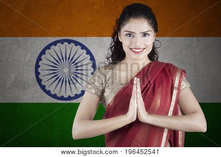 Beautiful Indian woman wearing a red saree clothes with Indian flag background
