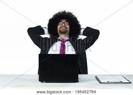 Portrait of a young African businessman with curly hair wearing formal suit and daydreaming with laptop on table