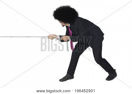 Young businessman pulling a chain and taking control with his strength isolated on white background