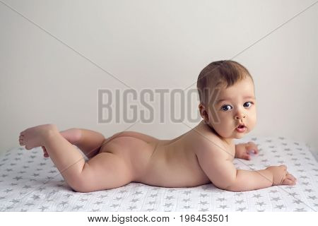 naked child lying on her belly on the diaper with stars