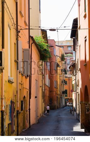 Narrow Street With Colourful Facades And Wooden Window Shutters In Bologna, Italy