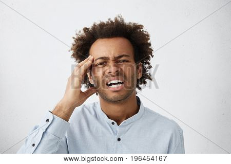 Picture Of Stressed Young Unshaven Afro-american Employee In Formal Shirt Having Painful Look, Touch