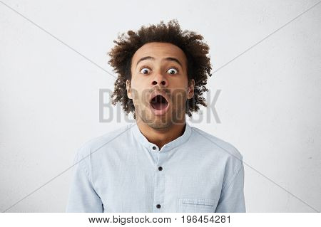 Omg, Wow. Picture Of Funny Emotional Dark-skinned Male Customer In Light-blue Shirt Gaping With Wide