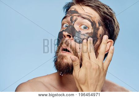 A young guy with a beard on a blue background applies clay cosmetic face mask.
